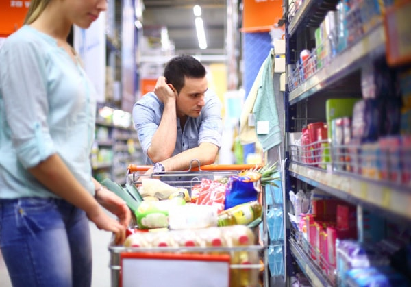 Discouraged couple shopping for groceries