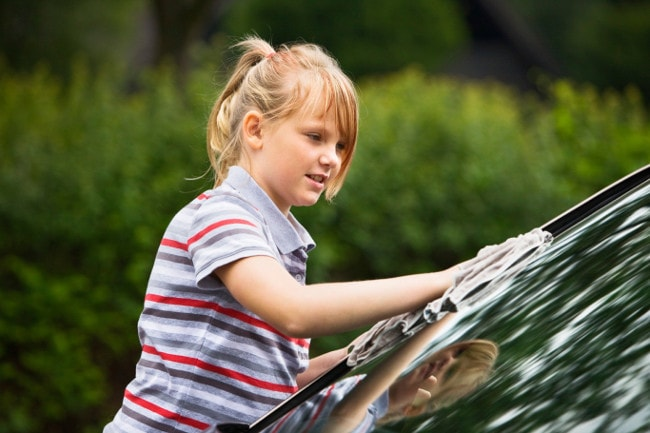 Young girl washing car