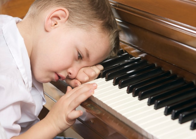 Young boy procrastinating at piano