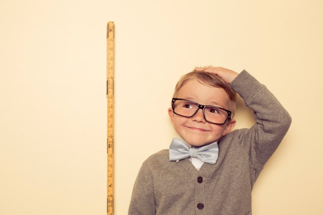 Boy with yard stick, measuring his height