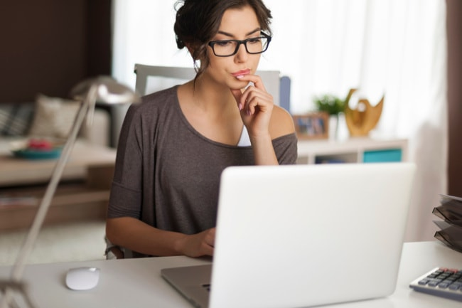 Woman at desk studying computer screen