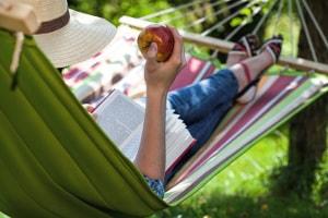 Woman reads book in hammock