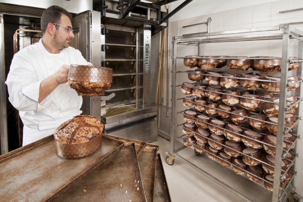 Baker loading cooling racks with bread