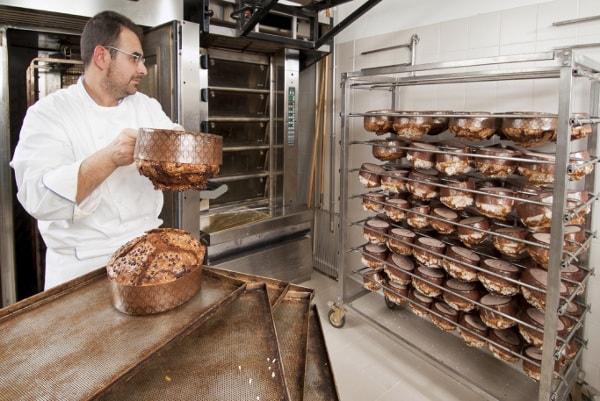 Baker loading cooling racks with bread